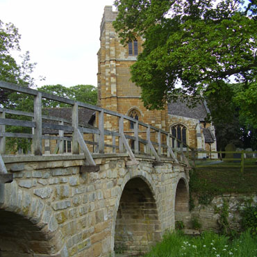 Medbourne pack horse bridge and church
