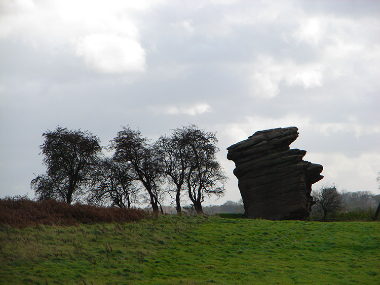 A silhouetted gritstone figure shows its face